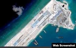 Satellite image of what is claimed to be an under-construction airstrip at Fiery Cross Reef in the Spratly islands in the disputed South China Sea. Web Screemshot theguardian.com