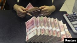 FILE - A clerk counts 100 Chinese yuan banknotes at a branch of China Merchants Bank in Hefei, Anhui province, April 20, 2015.