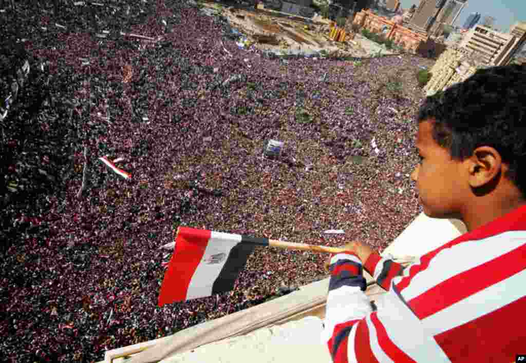 """A boy watches as pro-democracy supporters gather in Tahrir Square in Cairo on Friday. Egyptians held a nationwide """"Victory March"""" to celebrate the overthrow of Hosni Mubarak's 30-year rule one week ago (Reuters/Mohamed Abd El-Ghany)"""