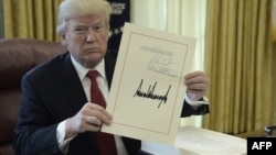 El presidente Donald J. Trump muestra un documento el día de la firma de la Ley de Recorte y Reforma de Impuestos en la Oficina Oval, el 22 de diciembre de 2017.