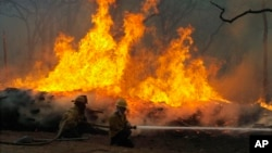 FILE - Firefighters battle a wildfire along Highway 71 near Smithville, Texas, Sept. 5, 2011.