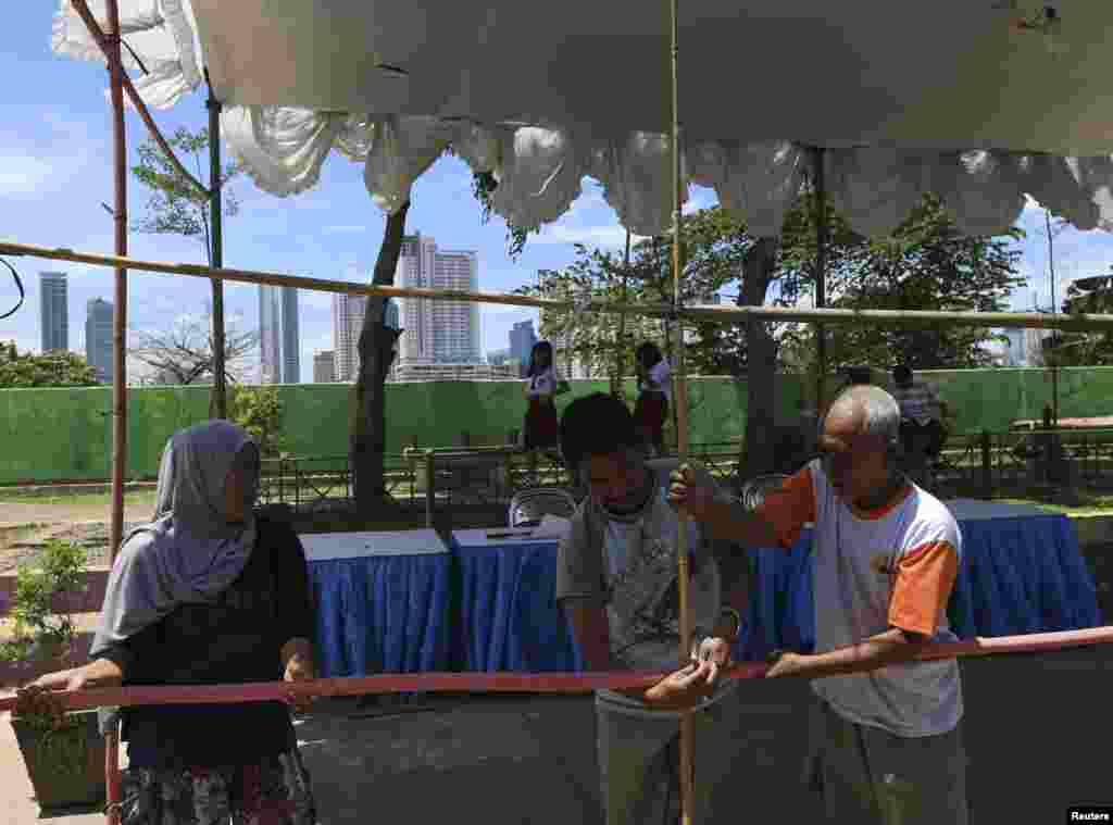 Volunteers make preparations at a polling station for the upcoming parliamentary election in Jakarta, April 8, 2014.