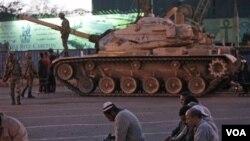 Para demonstran anti-pemerintah shalat Maghrib berjamaah di Lapangan Tahrir, Kairo sementara panser militer berjaga di dekatnya, Senin 31 Januari 2011.