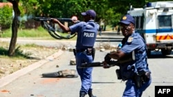 FILE - South African policemen fire rubber bullets at protesters in Mothotlung, Jan. 14, 2014.