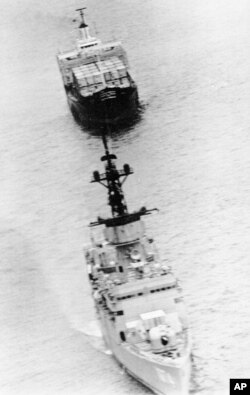 The U.S. merchant ship SS Mayaguez, rear, is towed away from Koh Tang island by the destroyer USS Harold E. Holt, May 15, 1975, after American military forces freed her from Cambodian captivity. (AP Photo)