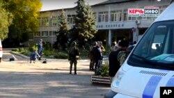 Polisi dan tim penyidik berdiri di dekat sekolah kejuruan, di Kerch, Krimea, 17 Oktober 2018, pasca penembakan. (Kerch Info News via AP)