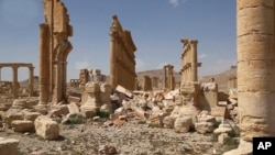 FILE - This photo released March 28, 2016, by the Syrian official news agency SANA shows some damage inflicted by Islamic State attacks at the ancient ruins of Palmyra, central Syria.