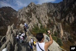 FILE – A North Korean man records video while climbing his country's Mount Kumgang in 2012.