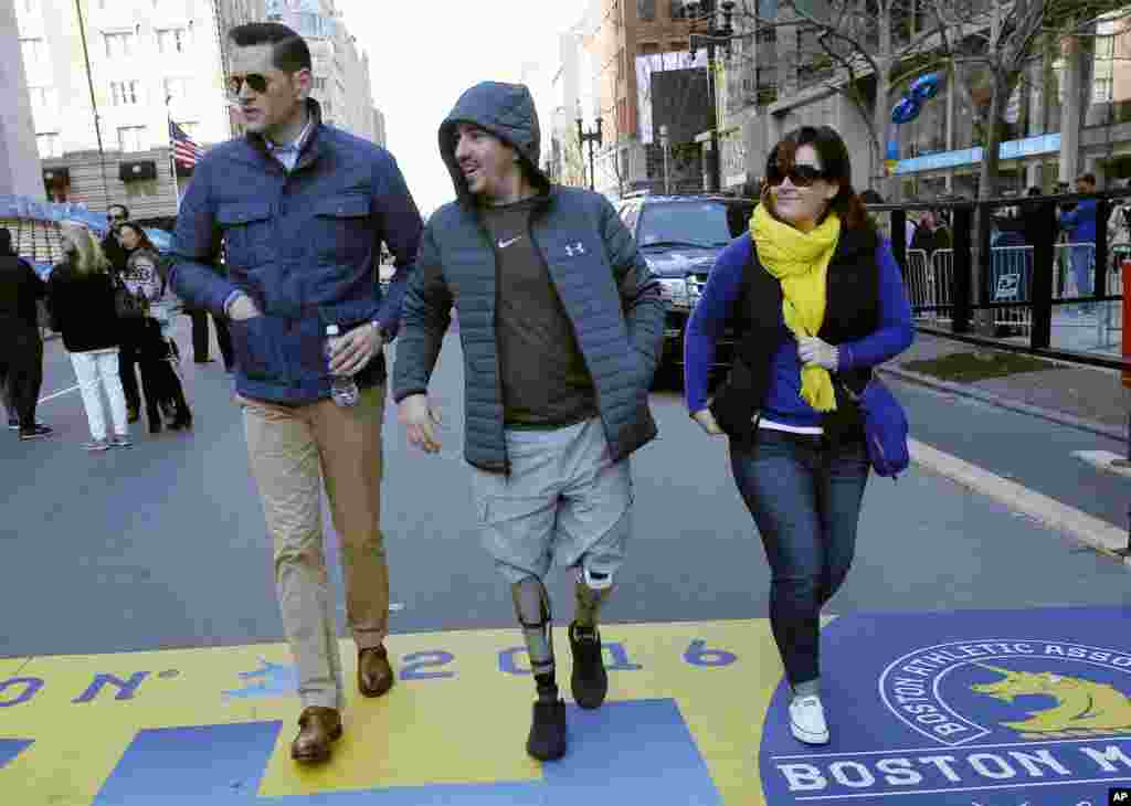 Boston Marathon bombing survivor Jeff Bauman, center, walks over the marathon finish line on the third anniversary of the bombings in Boston.