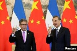 萨尔瓦多外长卡斯塔内达(左)和中国外长王毅在北钓鱼台国宾馆举行的建交仪式上举杯庆贺。(2018年8月21日)