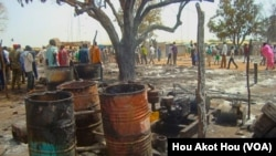 People walk past the charred remains of a shop in a market in Aweil, South Sudan, that was gutted by an overnight fire.