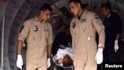 Egyptian military personnel help carry an injured 2nd Field Army solider into an ambulance, after a suicide bomber rammed his explosive-laden car into one of two buses carrying off-duty soldiers, killing at least 10 and wounding dozens more, security and
