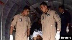 Nhân viên quân sự Ai Cập giúp đưa một binh sĩ bị thương lên xe cấp cứu sau vụ đánh bom gần El-Arish.