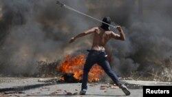 Un manifestante palestino lanza piedras durante enfrentamientos con soldados israelíes cerca del asentamiento de Bet El, en la Margen Occidental cerca de Ramallah.