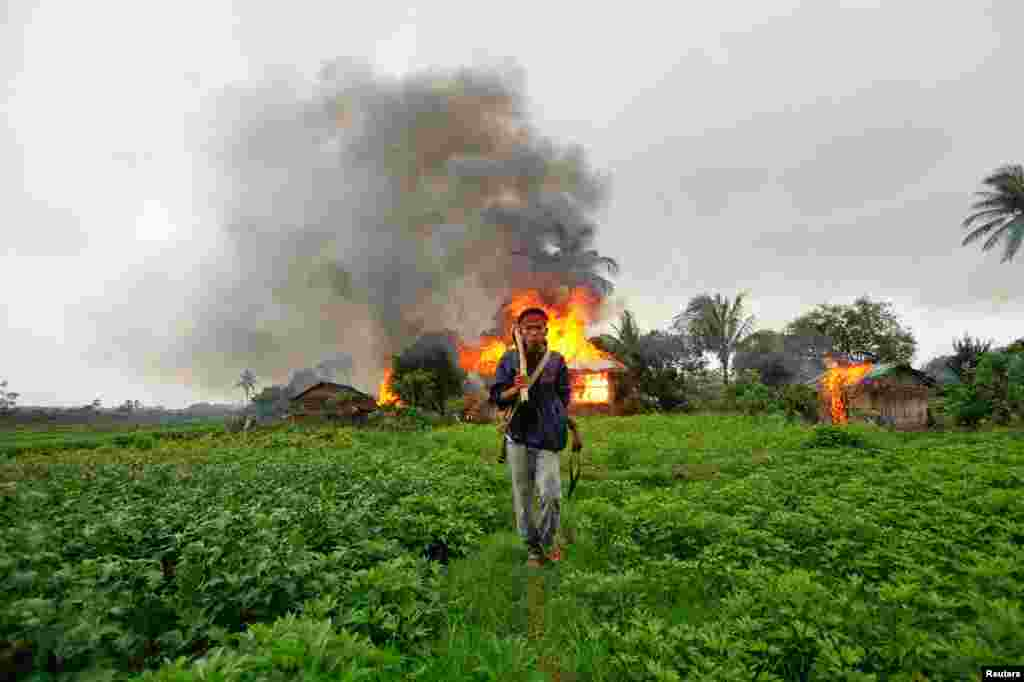 June 10: An ethnic Rakhine man with homemade weapons walks in front of houses that were set on fire during fighting between Buddhist Rakhine and Muslim Rohingya communities in Sittwe, Burma.