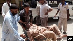 Warga yang menderita serangan panas dibawa ke rumah sakit di Karachi, Pakistan (23/6). (AP/Shakil Adil)