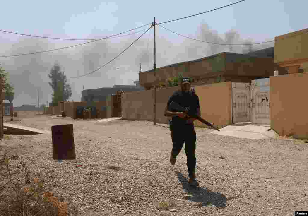 A fighter of the Asaib Ahl al-Haq Shi'ite militia takes cover from sniper fire, Sulaiman Bek, Sept. 1, 2014.