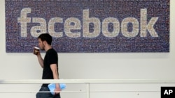 FILE - An employee walks past a sign at Facebook headquarters in Menlo Park, California, March 15, 2013. The social media giant is opening a new London office Monday.