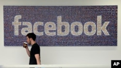 "FILE - A Facebook employee walks past a sign at Facebook headquarters in Menlo Park, California, March 15, 2013. A former employee has reportedly claimed the social media giant ""routinely suppressed news stories of interest to conservative readers."""