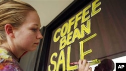 Carrie Warden, manager of The Sconelady's Coffee Shop, paints a sign for their fall coffee sale in Lawrence, Kan. Americans' confidence in the economy rose only slightly in October from September, according to a monthly survey, as they continue to grapple