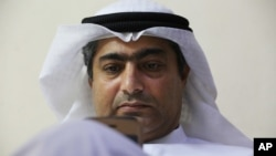 FILE - Human rights activist Ahmed Mansoor uses his iPhone in Ajman, United Arab Emirates, Aug. 25, 2016.