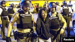 St. Louis County police officers arrest an anti-police demonstrator in Ferguson, Missouri, Aug. 11, 2015.
