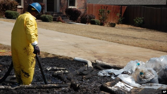 A worker cleans up oil in Mayflower, Ark., on Monday, Apr. 1, 2013, days after a pipeline ruptured and spewed oil over lawns and roadways.