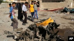 Warga setempat memeriksa lokasi serangan bom di wilayah Mashtal, Irak (27/10).