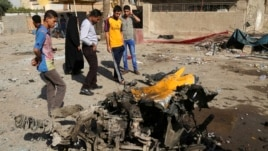Onlookers inspect the site of a car bomb attack in the capital's eastern Mashtal neighborhood, Iraq, Oct. 27, 2013.