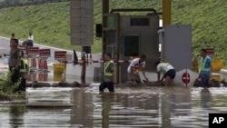 7月23日工人們在房山區一個公路收費站外堆沙包