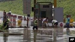 Các công nhân dùng những bao cát để chặn nước lũ tràn vào một trạm thu phí ở quận Phòng Sơn, Bắc Kinh, Trung Quốc, ngày 23/07/2012