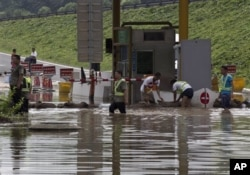 7月23日工人们在房山区一个公路收费站外堆沙包