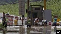 7月23日救災人員在北京房山區一個公路收費站外堆沙包