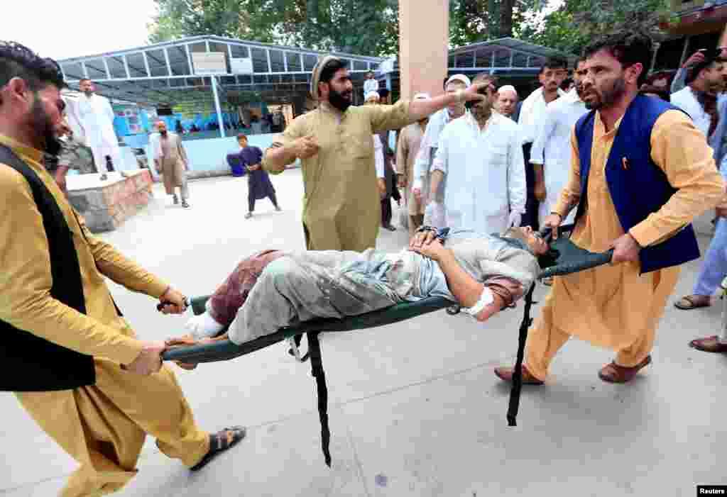 아프가니스탄 동부 낭가하르 주에서 선거 유세를 겨냥한 자살폭탄 테러사건이 발생한 후 아프간 남성들이 부상한 시민을 들 것에 실어 이동하고 있다.