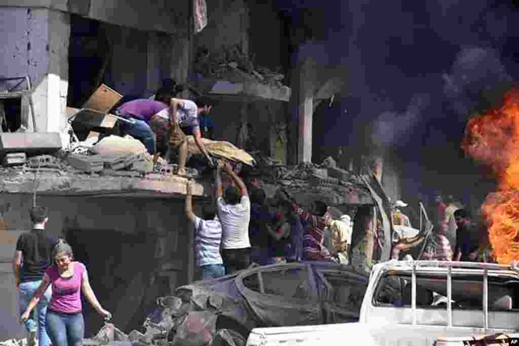 In this photo released by the Syrian official news agency SANA, Syrians carry the body of a victim from a building damaged in twin bombings struck Kurdish town of Qamishli, killing 44 people and wounding dozens more.