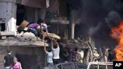 Warga Suriah mengevakuasi korban dari reruntuhan gedung akibat pemboman di kota Kurdi, Qamishli, yang menewaskan sedikitnya 44 orang, Rabu (27/7).