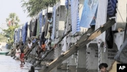 Residents staying at a concrete block, part of construction for an elevated train system, pass the time, in a flooded area on the outskirts of Bangkok November 11, 2011.