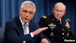 U.S. Secretary of Defense Chuck Hagel (L) speaks next to Chairman of the Joint Chiefs of Staff General Martin Dempsey during a press briefing at the Pentagon in Washington, Aug. 21, 2014.