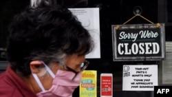Seorang perempuan mengenakan masker berjalan melewati tanda di jendela toko makanan yang tutup selama pandemi Covid-19 di Arlington, Virgina, 4 Mei 2020. (Foto: dok).