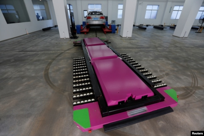 "FILE - A laser-guided ""parking robot"" moves to slide under a car at a research and development center in Shenzhen, China, June 29, 2016."