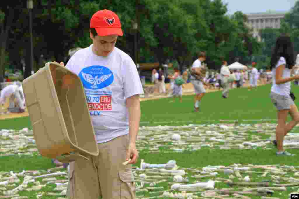 "A volunteer lays artificial bones at the ""One Million Bones"" installation on the National Mall, Washington, D.C, June 8, 2013. (Jill Craig/VOA)"