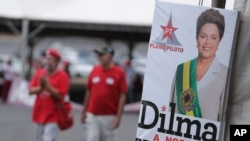 "People walk next to an official photography of Brazil's suspended President Dilma Rousseff, with a text written in Portuguese that reads ""Dilma our president,"" at a camp in Brasilia, Brazil, Sunday, Aug. 28, 2016."