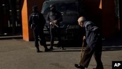 Un hombre pasa frente a policías armados montando guardia frente a la estación de trenes de Atocha, en Madrid.