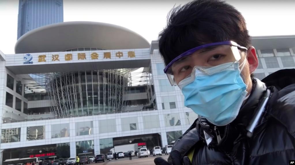 中国公民记者陈秋实在中国中部湖北省武汉市一场病毒性疫情中,在一家会议中心改建的临时医院前面。(2020年2月4日)