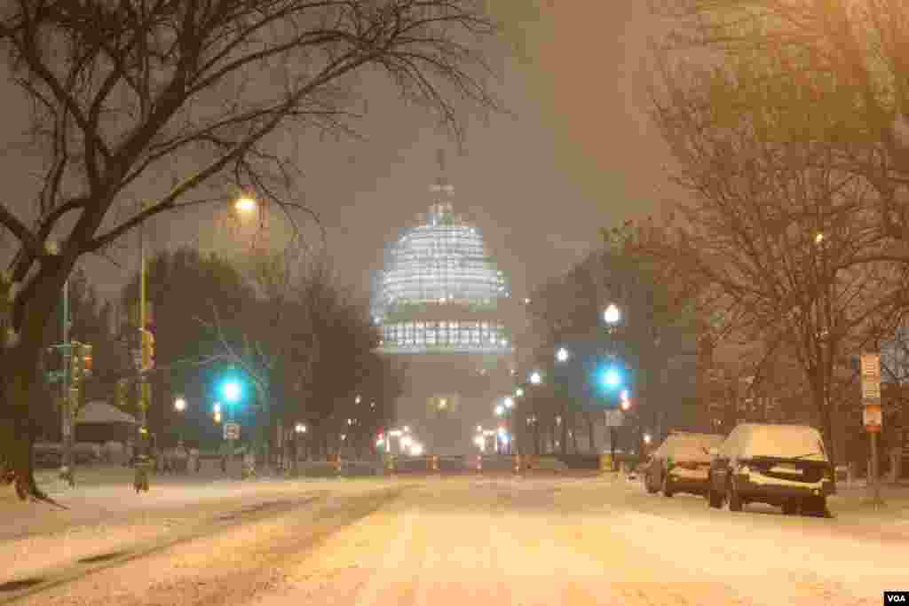 The illuminated dome of the US Capitol could be seen through the wind-blown snow at the intersection of 3rd and E. Capitol streets in Northeast Washington (P. Datcher/VOA)