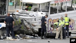Seattle Police investigators examine the front tire from a Ride the Ducks tour bus as it lies on the ground following a crash involving the tour bus and several other vehicles, Thursday, Sept. 24, 2015.