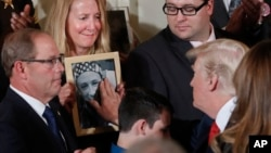 Jeanne Moser, center, of East Kingston, New Hampshire, watches as President Donald Trump reaches out to touch a photo of her son, Adam Moser, during an event to declare the opioid crisis a national public health emergency, in the East Room of the White House in Washington, Oct. 26, 2017.