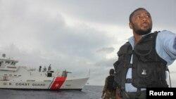 Un guardia costero jamaiquino vigila en Puerto Antonio, con el fondo de un guardacostas de Estados Unidos.