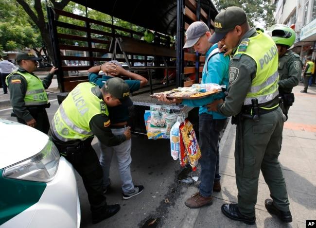 En esta foto del 22 de febrero de 2018, agentes de la policía colombiana detienen a migrantes venezolanos que no tienen identificación y permisos para vender productos, en Cúcuta, Colombia.