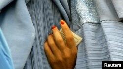 کابل میں ایک افغان خاتون نے صدارتی الیکشن میں ووٹ ڈالنے کے لیے اپنا شناختی کارڈ تھام رکھا ہے۔ فاٹل فوٹو